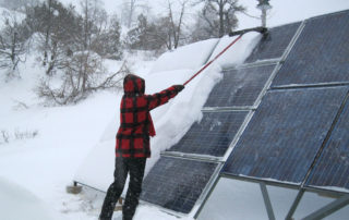 cleaning snow off solar array
